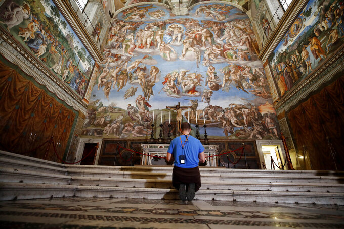 A visitor kneels in front of the Last Judgement fresco by the Italian Renaissance painter Michelangelo inside the Sistine Chapel of the Vatican Museums on the occasion of the museum's reopening, in Rome, Monday, May 3, 2021. The Vatican Museums reopened Monday to visitors after a shutdown following COVID-19 containment measures. (AP Photo/Alessandra Tarantino)