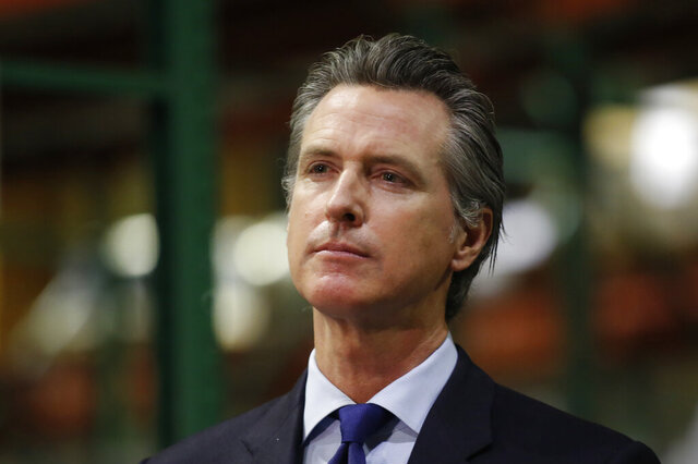 Gov. Gavin Newsom listens to a reporter's question during a news conference in Rancho Cordova, Calif., Friday, June 26, 2020. Newsom has pardoned 13 former prisoners, including three whose immigration status may benefit. He also commuted the sentences of 21 current inmates on Friday, including several who killed their victims and had been serving life-without-parole sentences. (AP Photo/Rich Pedroncelli, Pool)