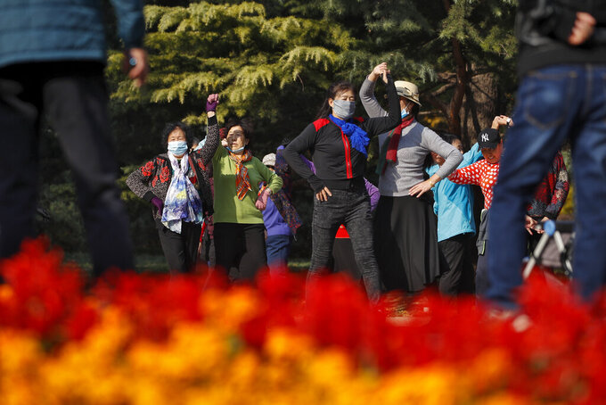 Women, some wearing face masks to help curb the spread of the coronavirus, practice social dance at a park in Beijing, Thursday, Nov. 5, 2020. China is suspending entry for most foreign passport holders who reside in Britain, reacting to a new surge of coronavirus cases in the United Kingdom. (AP Photo/Andy Wong)