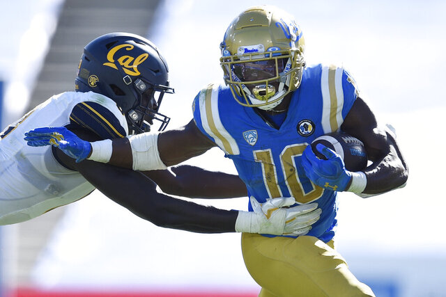 UCLA running back Demetric Felton, right, runs the ball while defended by California linebacker Kuony Deng during the second half of an NCAA college football game in Los Angeles, Sunday, Nov. 15, 2020. (AP Photo/Kelvin Kuo)
