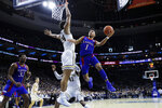 Kansas's Devon Dotson, right, goes up for a shot against Villanova's Jeremiah Robinson-Earl during the second half of an NCAA college basketball game, Saturday, Dec. 21, 2019, in Philadelphia. (AP Photo/Matt Slocum)