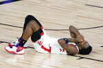 Toronto Raptors' OG Anunoby lies on the court after a collision during the second half of an NBA basketball conference semifinal playoff game against the Boston Celtics Sunday, Aug. 30, 2020, in Lake Buena Vista, Fla. (AP Photo/Ashley Landis)