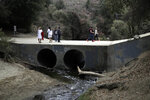 Visitors cross a bridge over Malibu Creek At the Malibu Creek State Park Thursday, Oct. 11, 2018, in Calabasas, Calif. Investigators will use ballistic testing to determine if a rifle carried by a burglary suspect was used in the killing of a camper at the California wilderness park. Authorities say 42-year-old Anthony Rauda had the gun and was dressed in black when he was arrested Wednesday after a search of a rugged canyon area near Malibu. (AP Photo/Marcio Jose Sanchez)