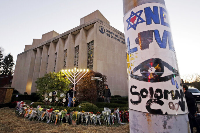 FILE - This Dec. 2, 2018, file photo shows a menorah at a memorial outside the Tree of Life Synagogue, where Robert Bowers killed worshippers in an Oct. 27 shooting, as people prepare for a celebration service at sundown on the first night of Hanukkah in the Squirrel Hill neighborhood of Pittsburgh. Jeffrey Clark Jr., whose relatives reported concerns about his behavior and far-right extremist rhetoric after the Pittsburgh synagogue massacre by Bowers, pleaded guilty to a federal gun charge Tuesday, July 23, 2019. (AP Photo/Gene J. Puskar, File)