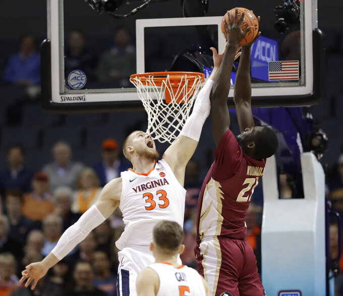 Florida State's Christ Koumadje (21) tries to dunk against Virginia's Jack Salt (33) during the first half of an NCAA college basketball game in the Atlantic Coast Conference tournament in Charlotte, N.C., Friday, March 15, 2019. (AP Photo/Chuck Burton)
