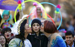 Actress Mia Kunis, center, is kissed by Amira Weeks, left, and Jacques Berguig during a parade for Kunis in Cambridge, Thursday, Jan. 25, 2018. Kunis was honored as