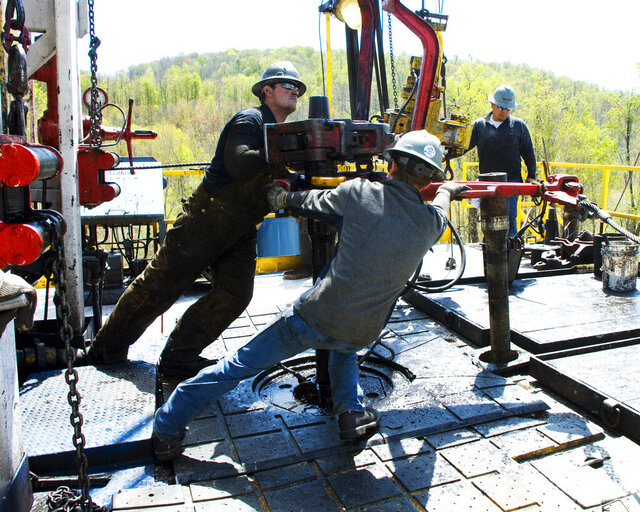 FILE - In this April 23, 2010, file photo, workers move a section of well casing into place at a Chesapeake Energy natural gas well site near Burlington, Pa., in Bradford County. Chesapeake Energy, a shale drilling pioneer that helped to turn the United States into a global energy powerhouse, has filed for bankruptcy protection. The Oklahoma City-based company said Sunday, June 28, 2020, that it was a necessary decision given its debt. Its debt load is currently nearing $9 billion.  (AP Photo/Ralph Wilson, File)