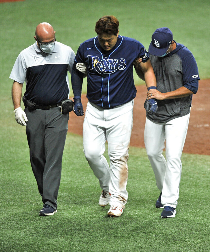 Tampa Bay Rays' Ji-Man Choi, center, is helped from the field by a trainer and manager Kevin Cash, right, after he was injured while scoring against the Boston Red Sox during the third inning of a baseball game Saturday, Sept. 12, 2020, in St. Petersburg, Fla. (AP Photo/Steve Nesius)