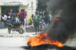 In this July 12, 2021, photo, a tire set on fire by supporters of former Senators Youri Latortue and Steven Benoit outside the courthouse in Port-au-Prince. The problems of two tiny Caribbean states, Cuba and Haiti, have vexed U.S. presidents for decades. Now, Haiti and Cuba are posing a growing challenge for President Joe Biden that could have political ramifications. (AP Photo/Matias Delacroix)