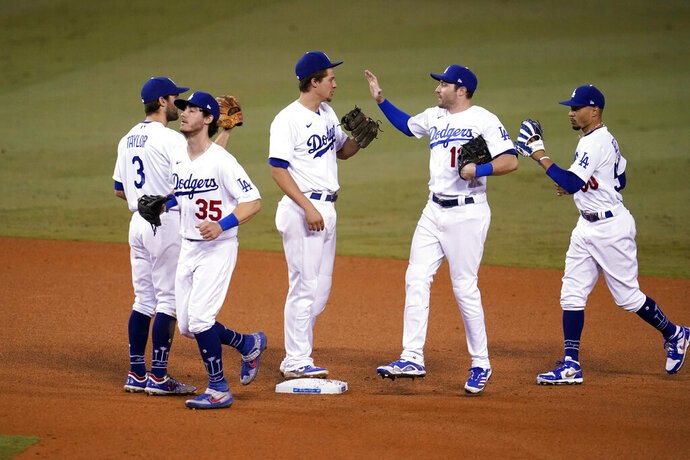The Los Angeles Dodgers celebrate a 5-1 win over the Oakland Athletics in a baseball game Thursday, Sept. 24, 2020, in Los Angeles. (AP Photo/Marcio Jose Sanchez)