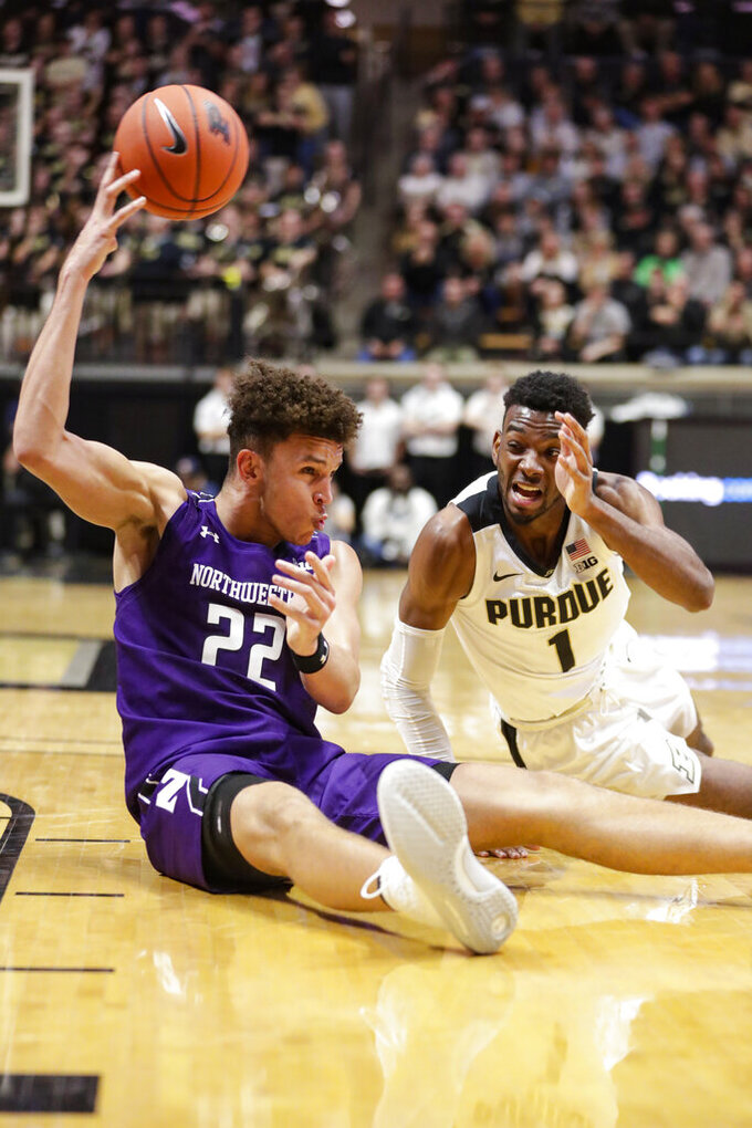 Northwestern forward Pete Nance (22) makes a pass as he goes to the floor with Purdue forward Aaron Wheeler (1) during the first half of an NCAA college basketball game in West Lafayette, Ind., Sunday, Dec. 8, 2019. (AP Photo/Michael Conroy)