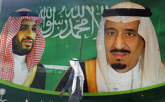 A man walks past a banner showing Saudi King Salman, right, and his Crown Prince Mohammed bin Salman, outside a mall in Jiddah, Saudi Arabia, Saturday, March 7, 2020. (AP Photo/Amr Nabil)