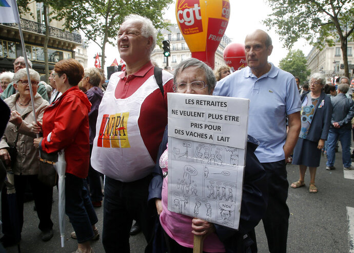 A retired woman holds a placard which reads