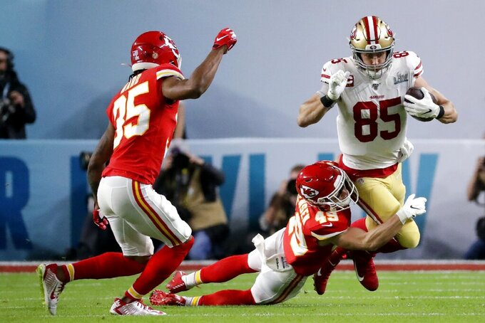 San Francisco 49ers' George Kittle (85) runs against Kansas City Chiefs' Daniel Sorensen (49) and Charvarius Ward during the first half of the NFL Super Bowl 54 football game Sunday, Feb. 2, 2020, in Miami Gardens, Fla. (AP Photo/Wilfredo Lee)