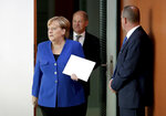 German Chancellor Angela Merkel, left, and German Finance Minister Olaf Scholz, center, arrive for the weekly cabinet meeting at the Chancellery in Berlin, Germany, Wednesday, Oct. 23, 2019. (AP Photo/Michael Sohn)