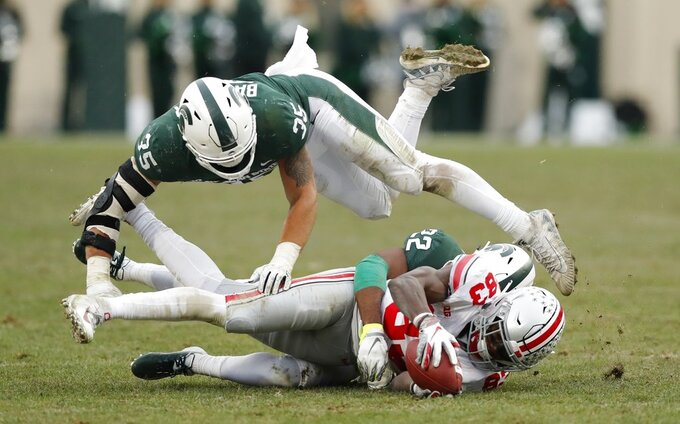 Michigan State linebacker Joe Bachie (35) flips over Michigan State cornerback Josiah Scott (22) as Scott tackles Ohio State wide receiver Terry McLaurin (83) during the second half of an NCAA college football game, Saturday, Nov. 10, 2018, in East Lansing, Mich. (AP Photo/Carlos Osorio)