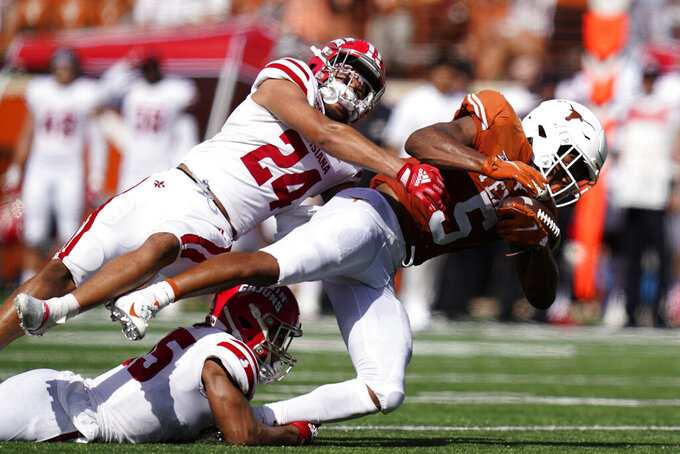 Texas running back Bijan Robinson (5) is hit by Louisiana-Lafayette safety Bralen Trahan (24) on a run during the first half of an NCAA college football game, Saturday, Sept. 4, 2021, in Austin, Texas. (AP Photo/Eric Gay)