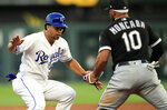 Kansas City Royals' Cheslor Cuthbert, left, is caught in a rundown and tagged out by Chicago White Sox third baseman Yoan Moncada (10) during the third inning of a baseball game at Kauffman Stadium in Kansas City, Mo., Tuesday, July 16, 2019. (AP Photo/Orlin Wagner)