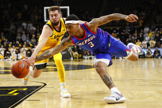 Iowa guard Jordan Bohannon, left, fights for a loose ball with DePaul guard Devin Gage (3) during the first half of an NCAA college basketball game, Monday, Nov. 11, 2019, in Iowa City, Iowa.(AP Photo/Charlie Neibergall)
