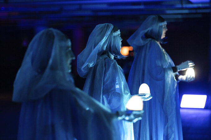 """This image shows the three Rhinemaidens in a scene from Lyric Opera of Chicago's """"Twilight: Gods,"""" an adaptation of Wagner's """"Götterdämmerung"""" staged in an underground parking garage in Chicago.  (Kyle Flubacker/Lyric Opera of Chicago via AP)"""