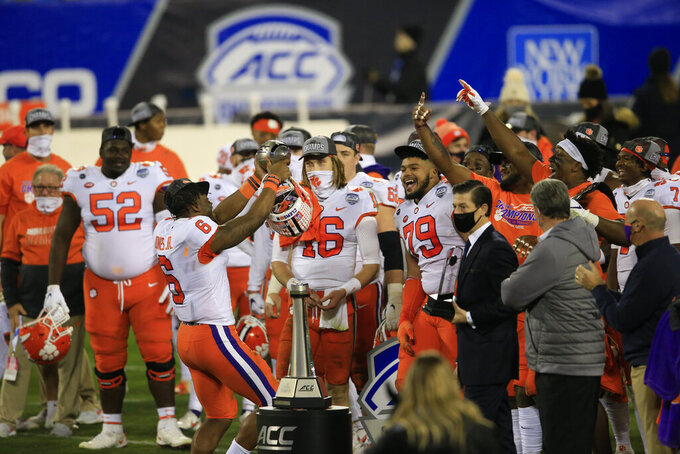 Clemson linebacker Mike Jones Jr. (6) holds up the trophy as he celebrates with teammates following their 34-10 victory over Notre Dame at the Atlantic Coast Conference championship NCAA college football game, Saturday, Dec. 19, 2020, in Charlotte, N.C. (AP Photo/Brian Blanco)
