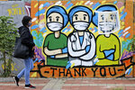 A woman walks past a mural honoring health care workers during the new coronavirus outbreak in Jakarta, Indonesia, Thursday, May 28, 2020. (AP Photo/Dita Alangkara)