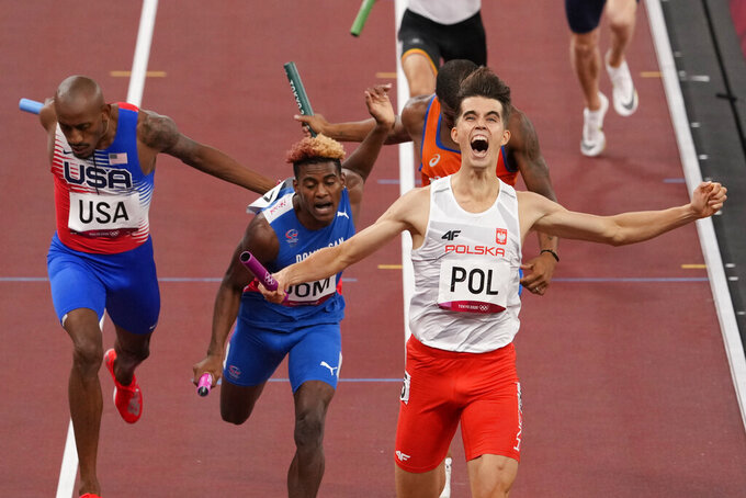 Patrick Grzegorzewicz of Poland celebrates as he crosses the finish line to win the 4 x 400-meter mixed relay at the 2020 Summer Olympics, Saturday, July 31, 2021, in Tokyo. (AP Photo/Charlie Riedel)