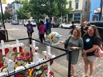 Sabrina Herman, gesturing, visits a makeshift memorial  on Wednesday, Aug. 14, 2019, outside Ned Peppers nightclub in the Oregon District entertainment neighborhood where on Aug. 4 a gunman killed nine people, in Dayton Ohio. Herman, 41, of Dayton, a hospital social worker, visited with her sister, Tara Luikart, right, of Washington Court House.  (AP Photo/Dan Sewell)