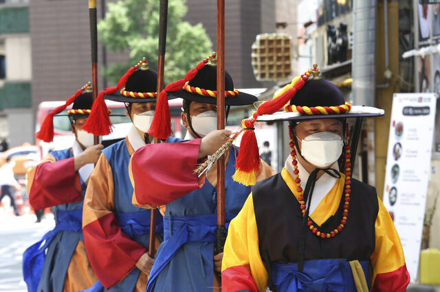 South Korean Imperial guards wearing face masks to help protect against the spread of the new coronavirus move near the Deoksu Palace in Seoul, South Korea, Friday, July 3, 2020. (AP Photo/Ahn Young-joon)