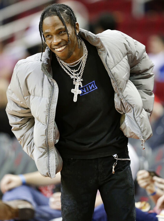 FILE - In this Feb. 9, 2018, file photo, hip hop artist Travis Scott watches warmups before an NBA basketball game between the Houston Rockets and the Denver Nuggets, in Houston. Big-name entertainers believe social injustice needs to be addressed during the Super Bowl and are ensuring the topic that ignited a political firestorm that engulfed the NFL will be in the spotlight. Scott has fallen under scrutiny for his upcoming Super Bowl appearance. The rapper agreed to participate in the halftime show if the NFL made a joint donation to an organization fighting for social justice.(AP Photo/Eric Christian Smith, File)
