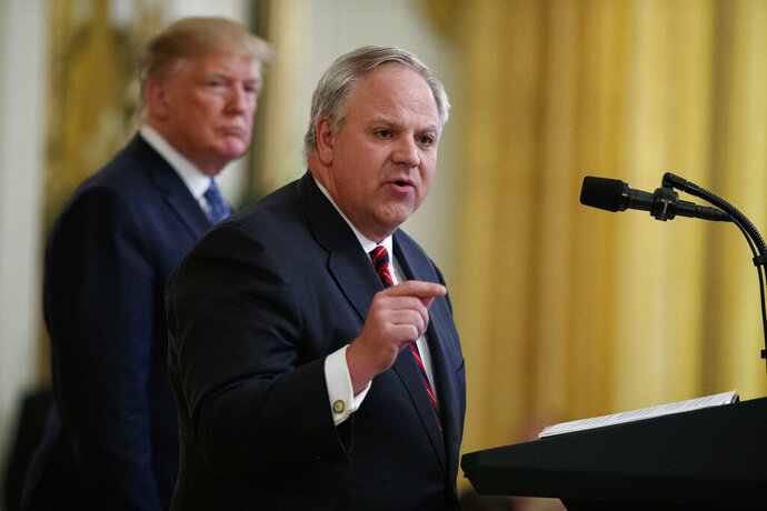 FILE - In this July 8, 2019 file photo President Donald Trump listens as Secretary of the Interior David Bernhardt speaks during an event on the environment in the East Room of the White House in Washington. A congressional committee is investigating whether the U.S. Interior Department helped an Arizona developer and supporter of President Donald Trump get a crucial permit. U.S. Rep. Raúl Grijalva is leading an investigation into the proposed 28,000-home development. Bernhardt had an unofficial meeting when he was deputy secretary with developer Mike Ingram, Arizona Diamondbacks co-owner and a prominent GOP donor. Interior officials deny politics played a part in the permit. (AP Photo/Evan Vucci, File)