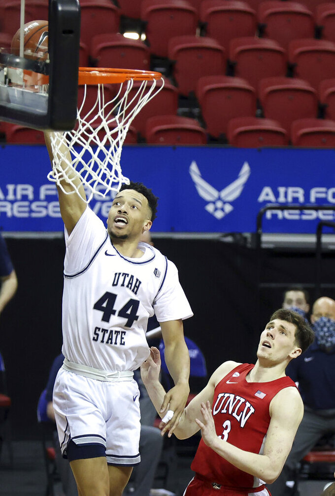 Utah State guard Marco Anthony (44) shoots as UNLV guard Caleb Grill (3) defends during the second half of an NCAA college basketball game in the quarterfinals of the Mountain West Conference men's tournament Thursday, March 11, 2021, in Las Vegas. (AP Photo/Isaac Brekken)