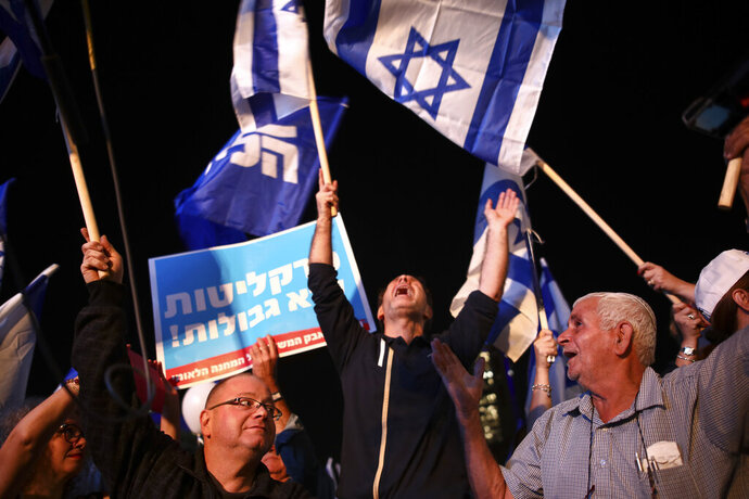 Israeli Prime Minister supporters cheerduring a support rally in Tel Aviv, Israel, Tuesday, Nov. 26, 2019. The sign with Hebrew reads: