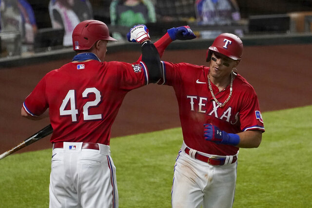Texas Rangers' Scott Heineman, left, and Derek Dietrich, right, celebrate a solo home run hit by Dietrich in the seventh inning of a baseball game against the Los Angeles Dodgers in Arlington, Texas, Friday, Aug. 28, 2020. (AP Photo/Tony Gutierrez)