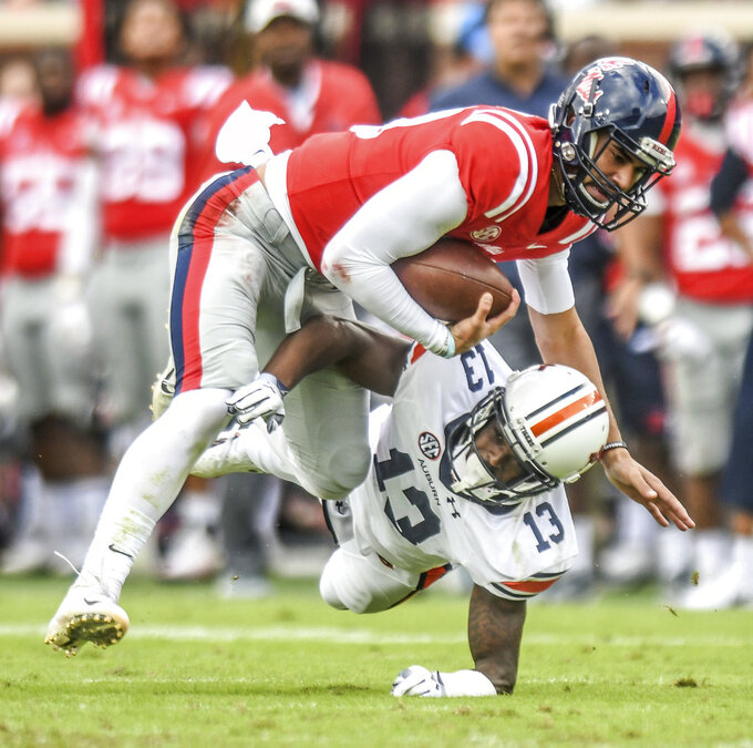 Mississippi quarterback Jordan Ta'amu (10) is tackled by Auburn defensive back Javaris Davis (13) during an NCAA college football game at Vaught-Hemingway Stadium in Oxford, Miss., Saturday, Oct. 20, 2018. (Bruce Newman/The Oxford Eagle via AP)