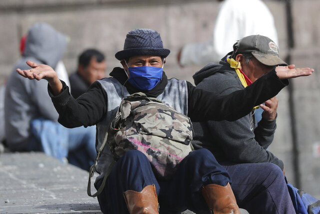 A man gestures to the camera as he rests in a public square in Quito, Ecuador, Friday, April 10, 2020. The government declared a