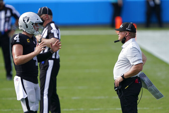 Las Vegas Raiders head coach Jon Gruden talks with quarterback Derek Carr during the second half of an NFL football game against the Carolina Panthers Sunday, Sept. 13, 2020, in Charlotte, N.C. (AP Photo/Brian Blanco)