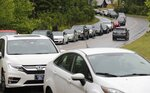 Cars line up on Pine Plaza Drive for gas at the Costco in Apex, N.C., Wednesday, May 12, 2021.  Several gas stations in the Southeast reported running out of fuel, primarily because of what analysts say is unwarranted panic-buying among drivers, as the shutdown of a major pipeline by hackers entered its fifth day. (Ethan Hyman/The News & Observer via AP)