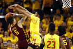 Minnesota guard Amir Coffey, left, attempts to shoot as he is pressured by Maryland forward Ricky Lindo Jr. in the second half of an NCAA college basketball game, Friday, March 8, 2019, in College Park, Md. (AP Photo/Patrick Semansky)