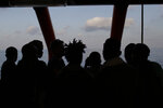 FILE - In this Sept. 13, 2019, file photo, rescued migrants are silhouetted as they look out at the horizon aboard the Ocean Viking, in the Mediterranean Sea. The U.N. refugee agency is investigating why Malta last week allegedly asked the Libyan coast guard to intercept a migrant boat in a zone of the Mediterranean under Maltese responsibility, in possible violation of maritime law, a U.N. official said Tuesday, Oct. 22, 2019. (AP Photo/Renata Brito, File)