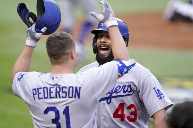 Los Angeles Dodgers Edwin Rios celebrates his home run with Joc Pederson against the Atlanta Braves during the first inning in Game 3 of a baseball National League Championship Series Wednesday, Oct. 14, 2020, in Arlington, Texas. (AP Photo/Eric Gay)