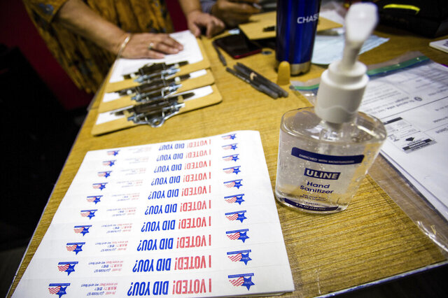 FILE - In this March 17, 2020, file photo, hand sanitizer and stickers are set up at a polling station in Chicago. Election Day voters, whose numbers have waned in recent years because of expanded options for casting ballots, likely will be reduced even further this year with a surge in vote-by-mail popularity during a pandemic. Ballots to those who applied to vote by mail started going out on Thursday, Sept. 24, 2020, to a record 1.82 million voters thus far, according to the Illinois State Board of Elections. Legislation adopted last spring ensured widespread publicity for the practice because of the coronavirus outbreak. ( James Foster/Chicago Sun-Times via AP, File)