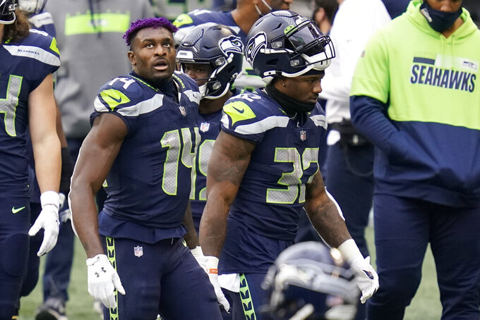 Seattle Seahawks wide receiver DK Metcalf (14) and running back Chris Carson (32) stand on the sideline near the end of the first half of an NFL football game against the New York Giants, Sunday, Dec. 6, 2020, in Seattle. (AP Photo/Elaine Thompson)