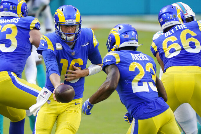 Los Angeles Rams quarterback Jared Goff (16) hands the ball to running back Cam Akers (23), during the second half of an NFL football game against the Los Angeles Rams, Sunday, Nov. 1, 2020, in Miami Gardens, Fla. (AP Photo/Wilfredo Lee)