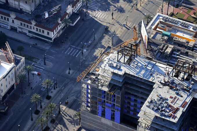 FILE - In this Sunday, Oct. 20, 2019, aerial file photo, one of two large cranes from the Hard Rock Hotel construction collapse is seen hanging over the edge above Canal Street after crashing down, after being detonated for implosion in New Orleans. New Orleans officials marked the return of two-way traffic to a major New Orleans thoroughfare Wednesday, April 28, 2021, more than 18 months after the partial collapse of the hotel under construction at the edge of the French Quarter killed three people and halted traffic and commerce on a section of historic Canal Street. (AP Photo/Gerald Herbert, File)