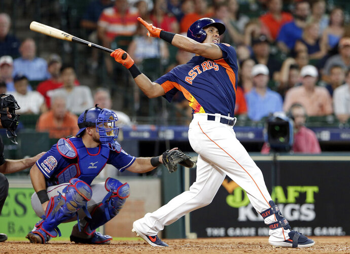 Houston Astros left fielder Michael Brantley, right, watches his home run in front of Texas Rangers catcher Jeff Mathis, left, during the eighth inning of a baseball game Sunday, July 21, 2019, in Houston. (AP Photo/Michael Wyke)