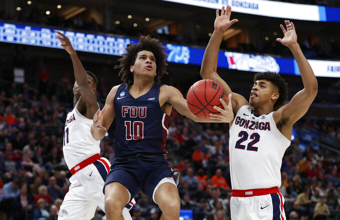 Fairleigh Dickinson guard Brandon Powell (10) drives between Gonzaga guard Joel Ayayi (11) and forward Jeremy Jones (22) during the second half of a first-round game in the NCAA men's college basketball tournament Thursday, March 21, 2019, in Salt Lake City. (AP Photo/Jeff Swinger)