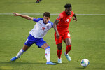Canada's Alphonso Davies (19) goes past Haiti's Steeven Saba (10) during the first half of a World Cup qualifying soccer match Tuesday, June 15, 2021, in Bridgeview, Ill. (AP Photo/Kamil Krzaczynski)