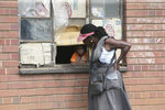 A woman talks to a child through a window in Harare, Thursday May 28, 2020. Manhunts have begun after hundreds of people, some with the coronavirus, fled quarantine centres in Zimbabwe and Malawi while authorities worry they will spread COVID-19 in countries whose health systems can be rapidly overwhelmed.(AP Photo/Tsvangirayi Mukwazhi)