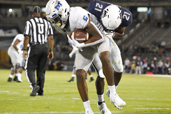 Middle Tennessee State's Jimmy Marshall, front left, scores a touchdown while Connecticut's Jeremy Lucien, right, defends in the first half of an NCAA college football game Friday, Oct. 22, 2021, in East Hartford, Conn. (Jessica Hill/Hartford Courant via AP)